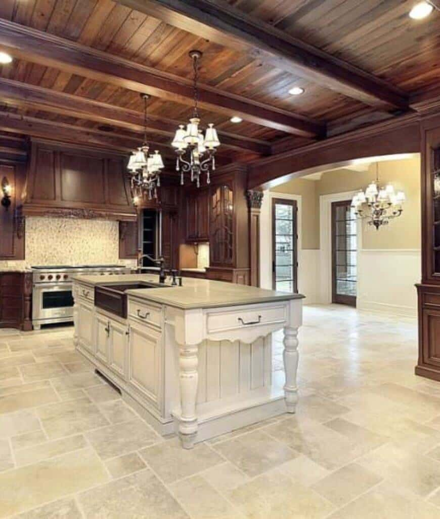 Expansive kitchen with a white central island lighted by vintage chandeliers that hung from the wood plank ceiling blending with the wooden cabinetry.