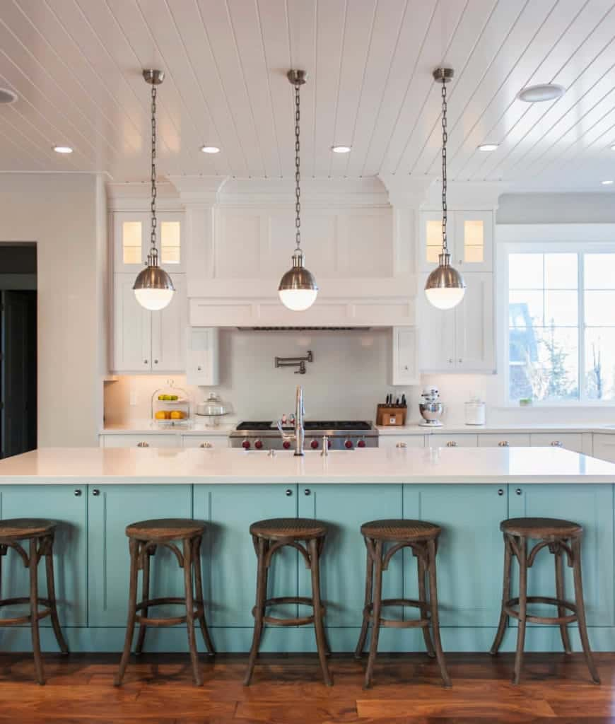 Beach style kitchen accented by an aqua breakfast bar aligned with wooden barstools. It is illuminated by glass globe pendants that hung from the white shiplap ceiling.