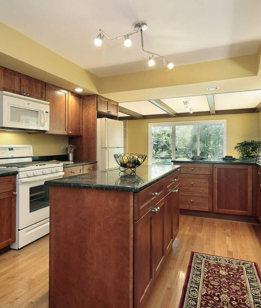 Yellow kitchen with white appliances and wooden cabinetry that match with the breakfast island topped with a black marble counter and lighted by a chrome pendant.
