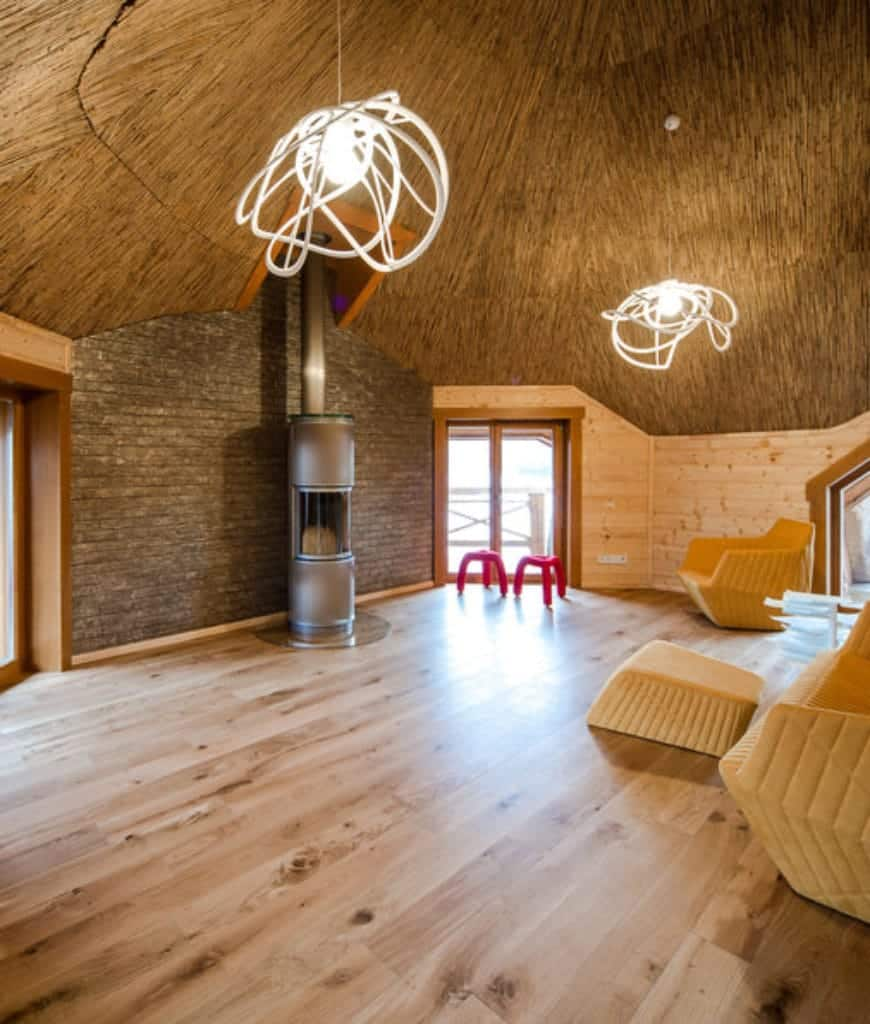 An all wood living room offers a freestanding fireplace and sleek tan sofa set lighted by a pair of unique spiral pendants that hung from the wooden dome ceiling.
