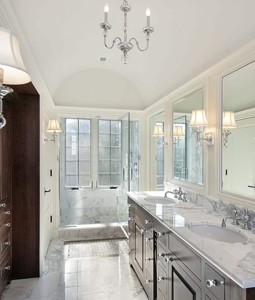 This master bathroom features a walk-in shower and dual sink vanity with dark wood cabinets fitted with glass knobs. It has a marble countertop that matches with the flooring and walls for a cohesive look.