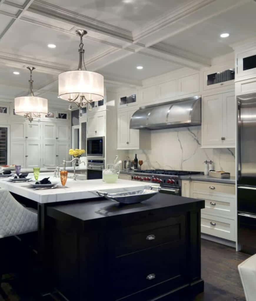 Modern kitchen with stainless steel appliances and a marble top island bar lighted by drum chandeliers that hung from the coffered ceiling.