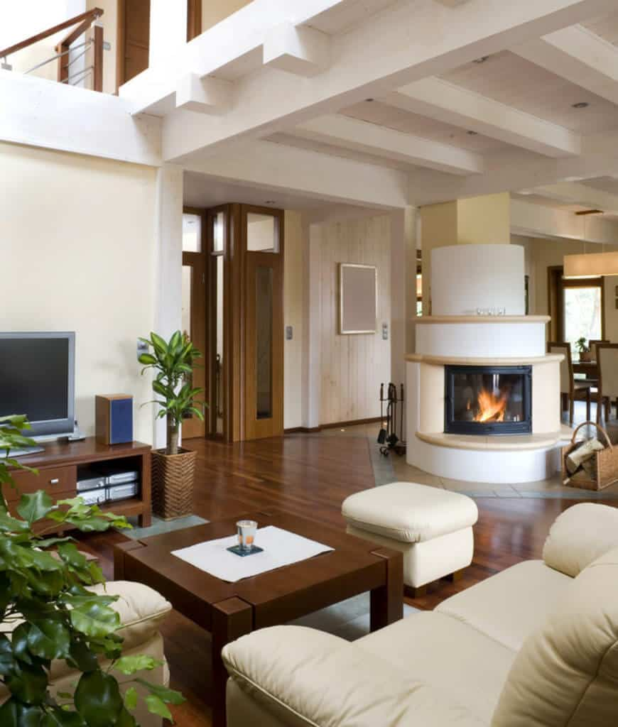 Southwestern living room showcases a fireplace that complements with the leather sofas and stool paired with a wooden coffee table over hardwood flooring.