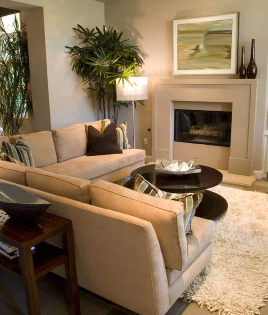 Fresh living room decorated with a lovely abstract wall art that hung above the fireplace lighted by a modern floor lamp. It has a round coffee table and beige L-shaped sofa accented with brown and striped pillows.