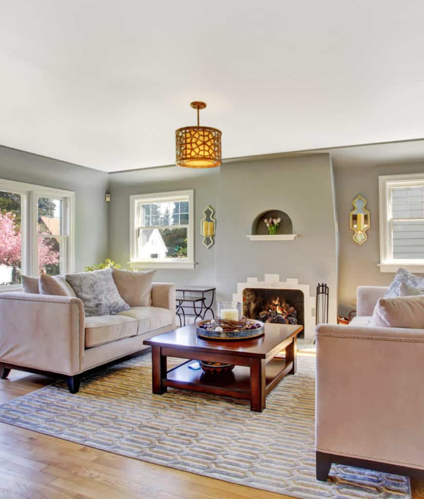 Charming living room offers beige velvet sofas and fireplace lighted by mirrored sconces and an ornate semi-flush mount light that hung over the wooden coffee table.