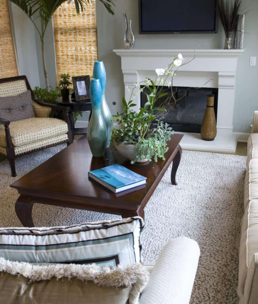 A closeup look in this living room with white fireplace and a wooden coffee table topped with plants and gorgeous blue vases.