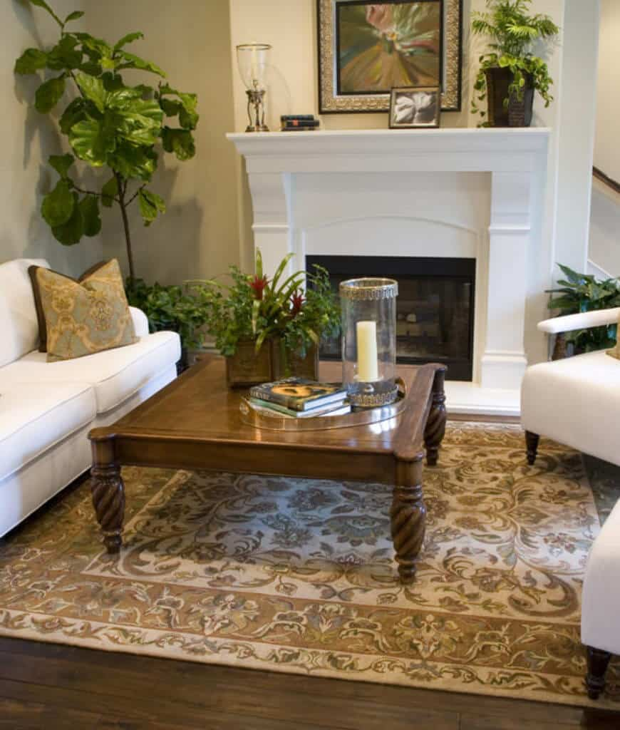 Tropical living room offers a wooden coffee table and white seats with patterned pillows that complement with the rug.