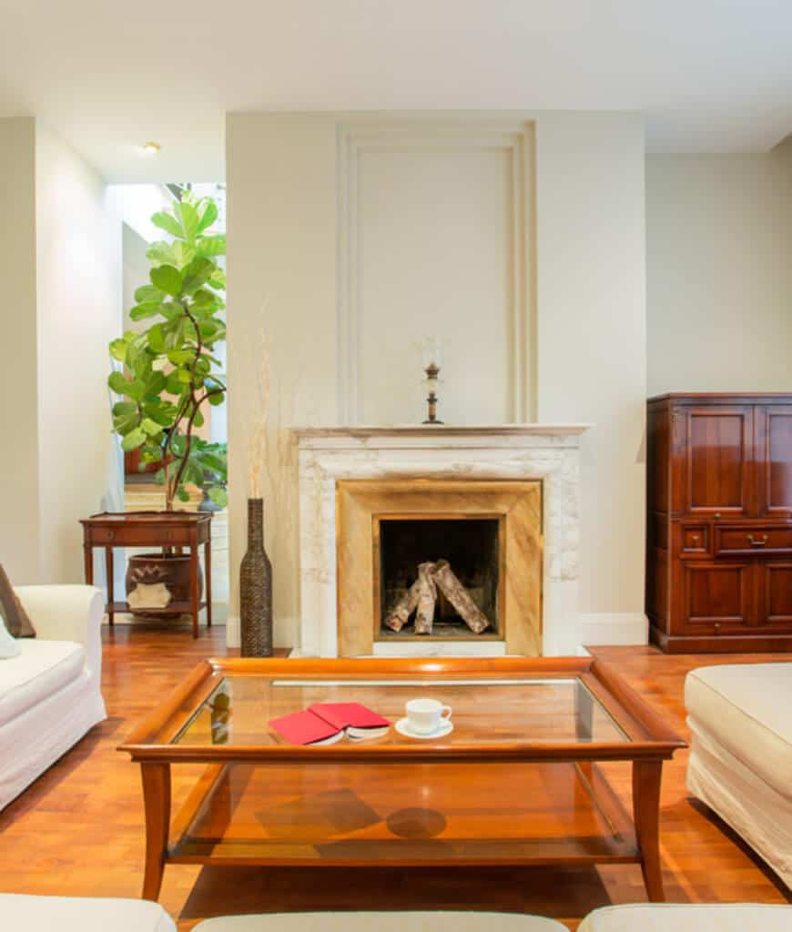 Warm living room boasts a luxury fireplace with a vase on its side along with a glass top coffee table that complements with the hardwood flooring.