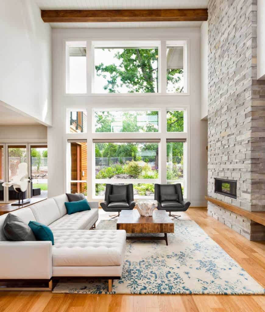 High ceiling living room offers a natural wood coffee table and white tufted sofa contrasted with black chairs across the fireplace fitted on the brick pillar.