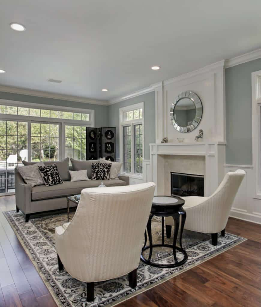 Traditional living room decorated with a round beveled mirror that hung above the fireplace framed with white mantel and marble surround tiles.