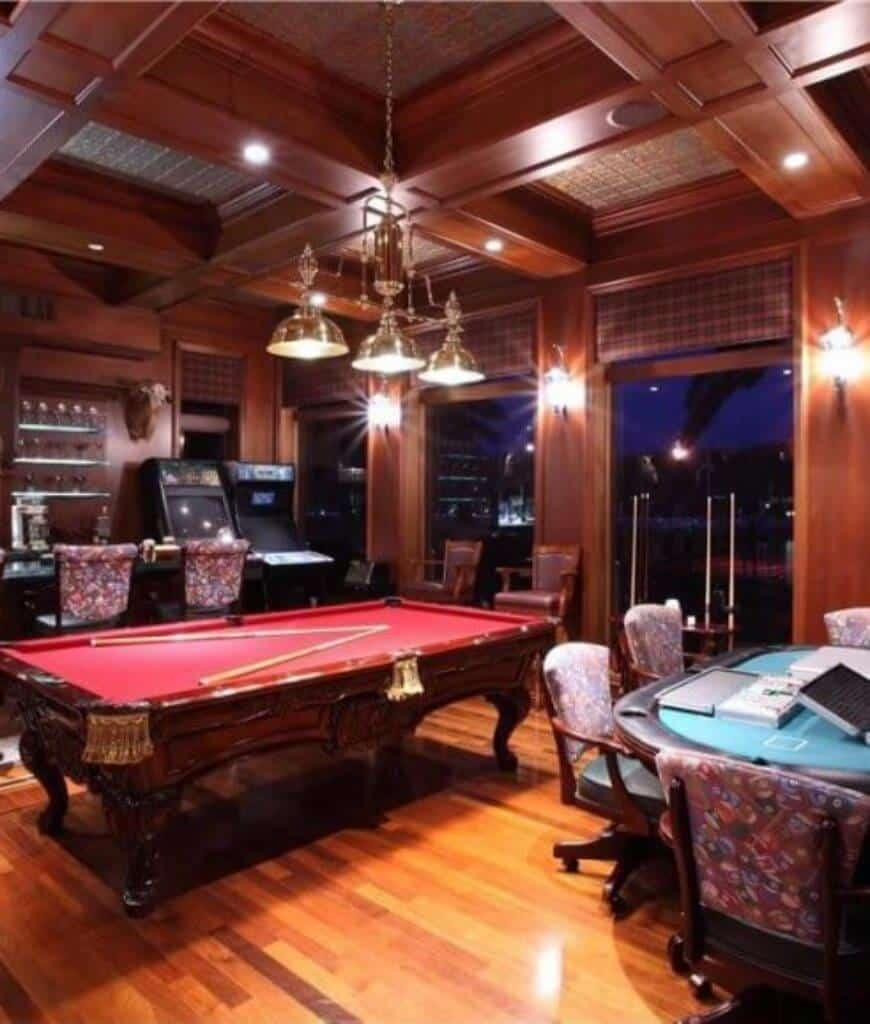Cozy game room features rich hardwood flooring and coffered ceiling with a hanging chrome pendant. It has poker and pool tables along with arcade machines next to the bar area.