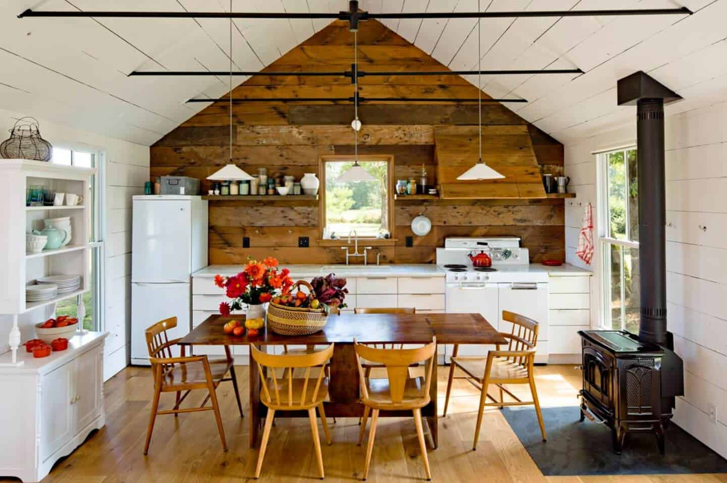 A pair of pendant lights that hung from the cathedral ceiling illuminates this eat-in kitchen with white appliances and cabinetry along with a wooden dining set that sits next to the freestanding fireplace.