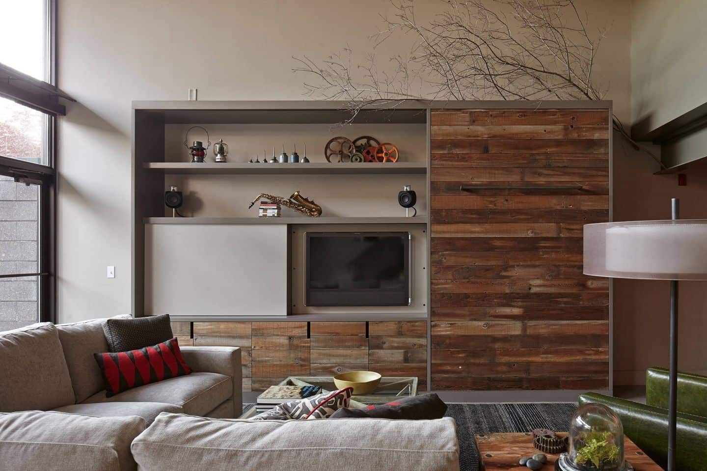 This living room boasts a wood paneled wall fitted with open shelving and television. It has an L-shaped sectional and glass top coffee table that sits on a gray rug.