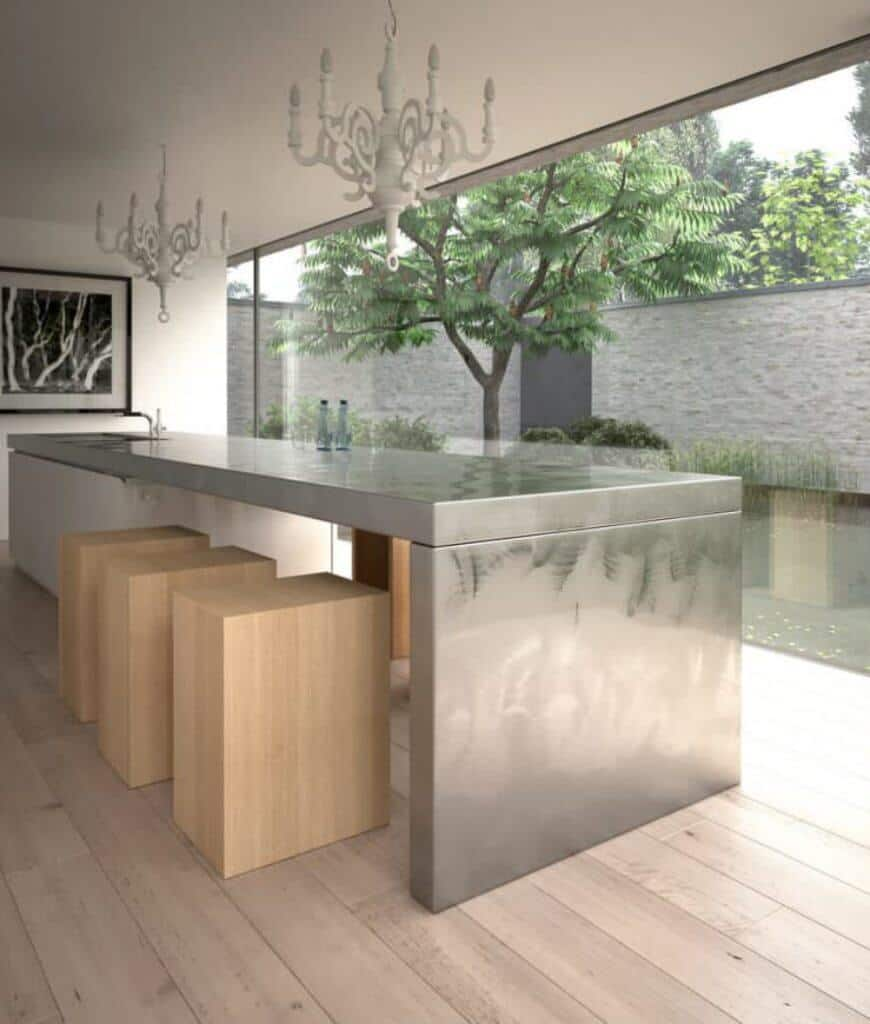 Contemporary kitchen showcases panoramic windows and classy white chandeliers that hung over the stainless steel island bar paired with smooth and sleek stools.