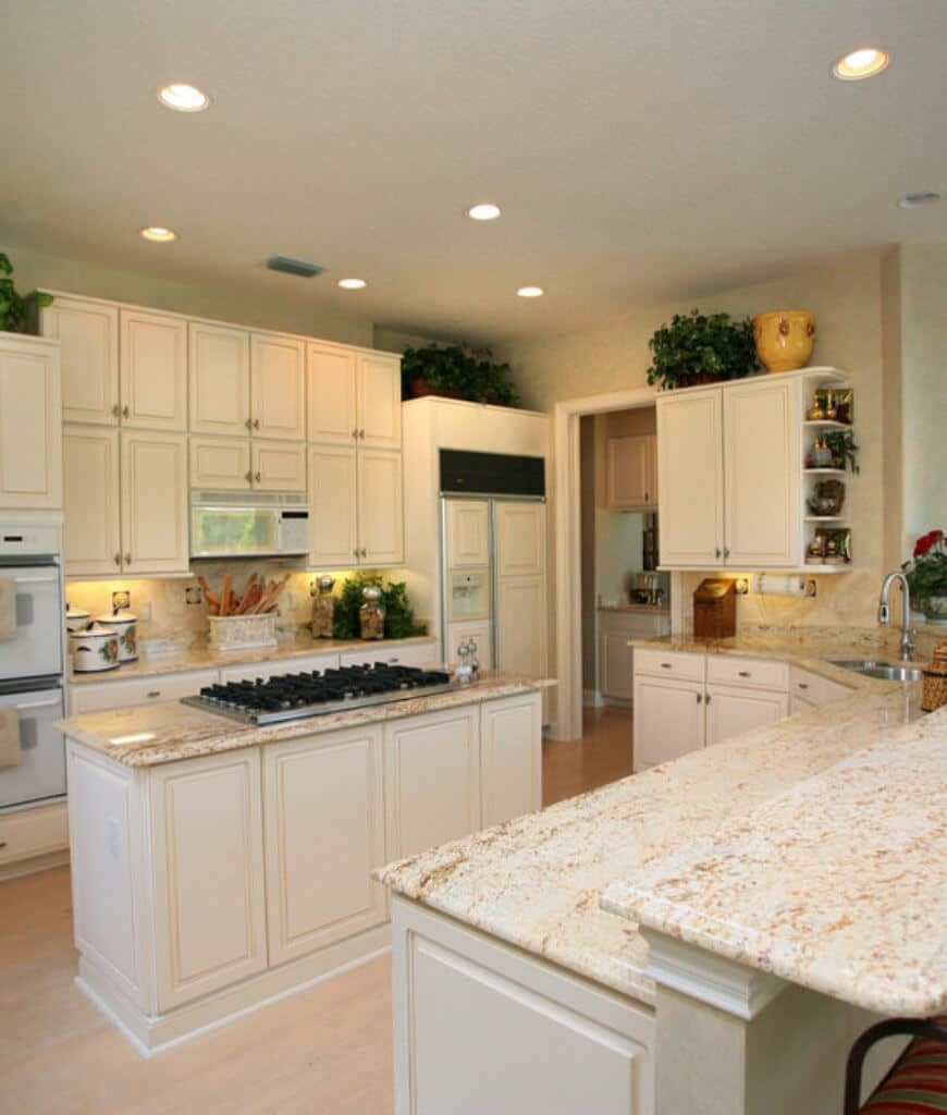 A lovely kitchen sporting a cohesive design. It has a central kitchen island with built-in cooktop and two-tier peninsula with marble countertops.