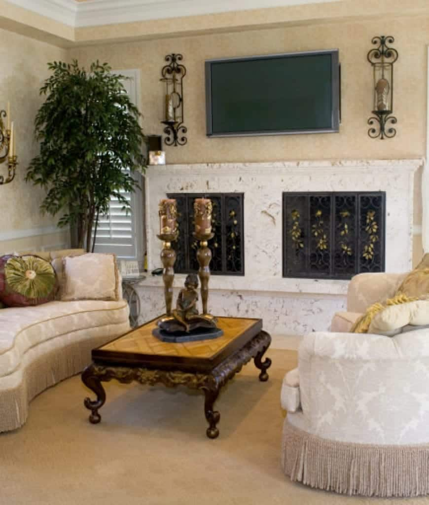 Mediterranean living room with elegant curved sofas and a flat panel TV that hung above the marble fireplace covered with ornate wrought iron screens.