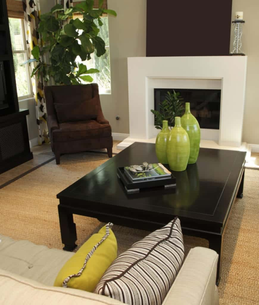 Gorgeous green vases on a black coffee table stand out in this living room with a brown armchair and sleek fireplace topped with a metal candle holder.