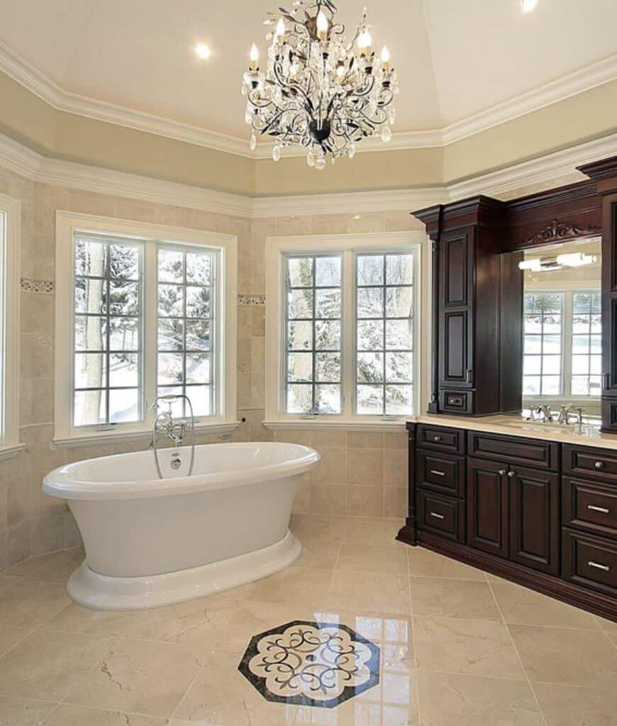 A freestanding bathtub and wooden sink vanity filled this primary bathroom illuminated by a gorgeous chandelier and recessed lights mounted on the dome ceiling.
