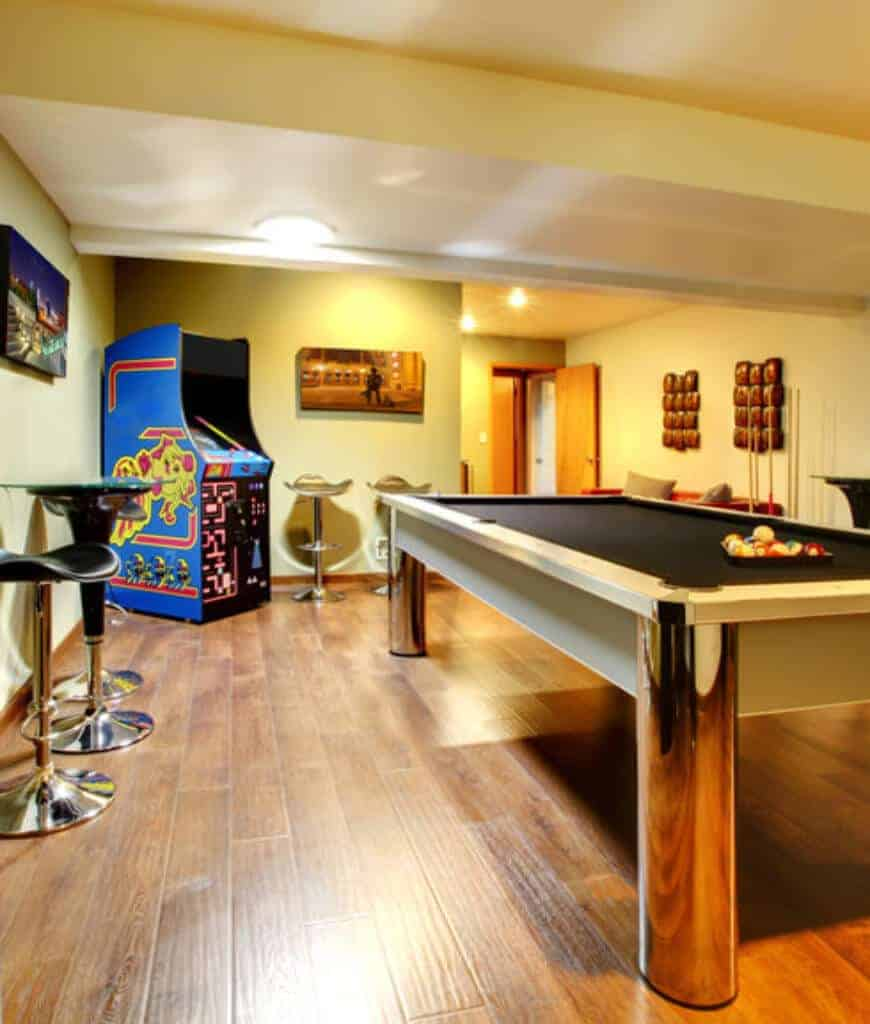 Yellow game room with a contemporary pool table and a Ms. Pac-Man in the corner. There are chrome bar stools on the sides accented with lovely wall arts.