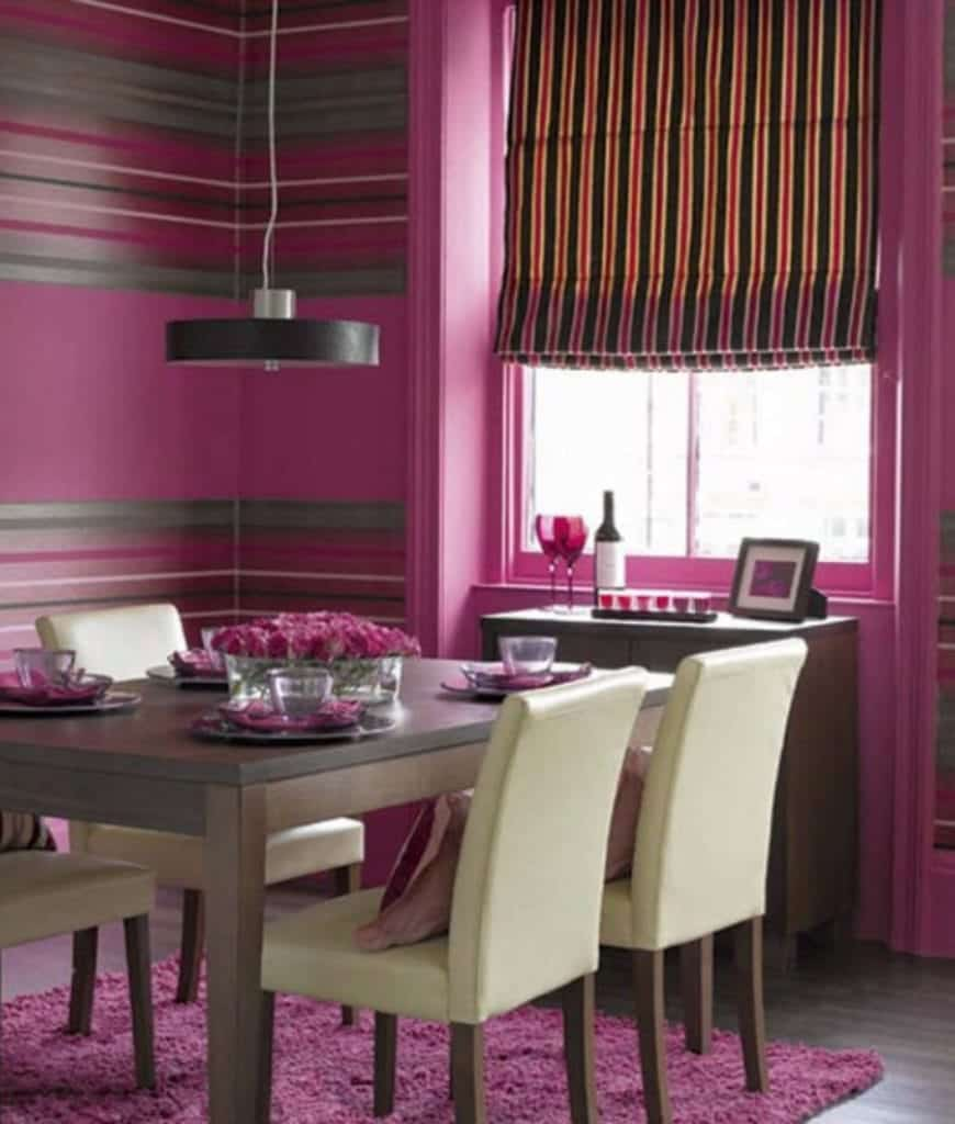 Charming dining room offers a glazed window covered in striped roman shade along with hardwood flooring topped by a pink shaggy rug.