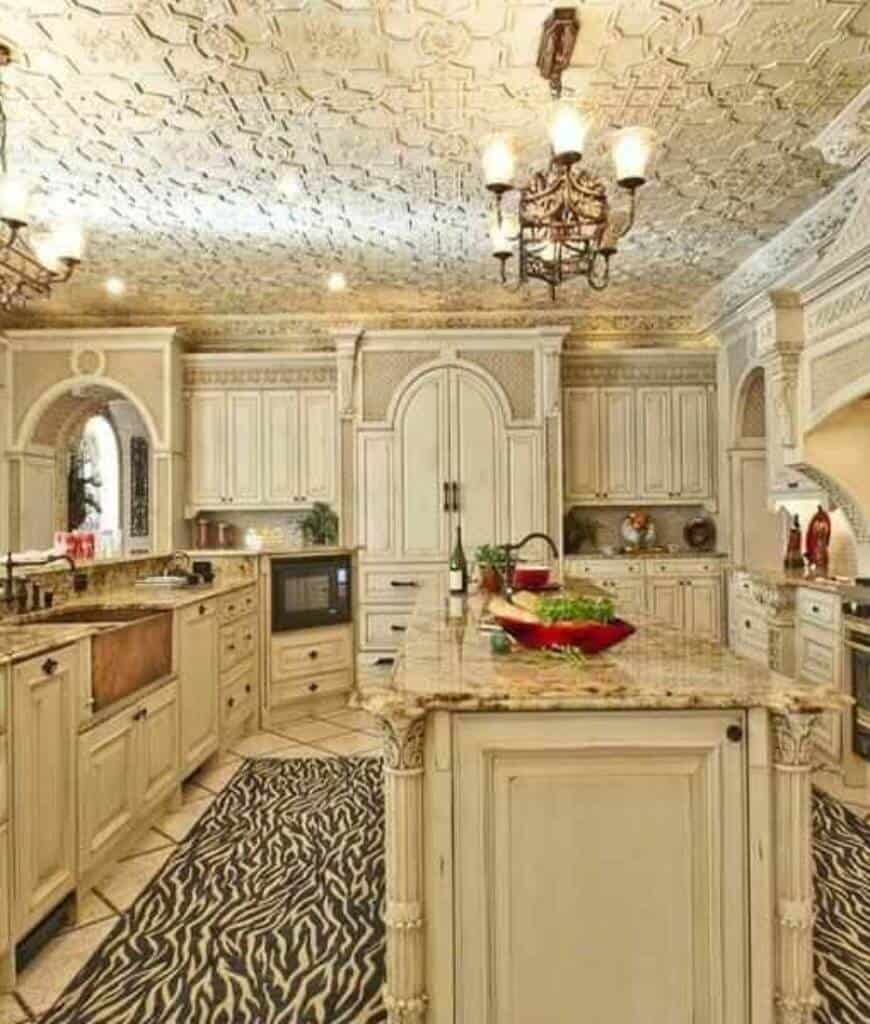 Deluxe kitchen showcases ornate ceiling with hanging chandelier and white cabinetry accented with a striking black area rug that lays on the tiled flooring.