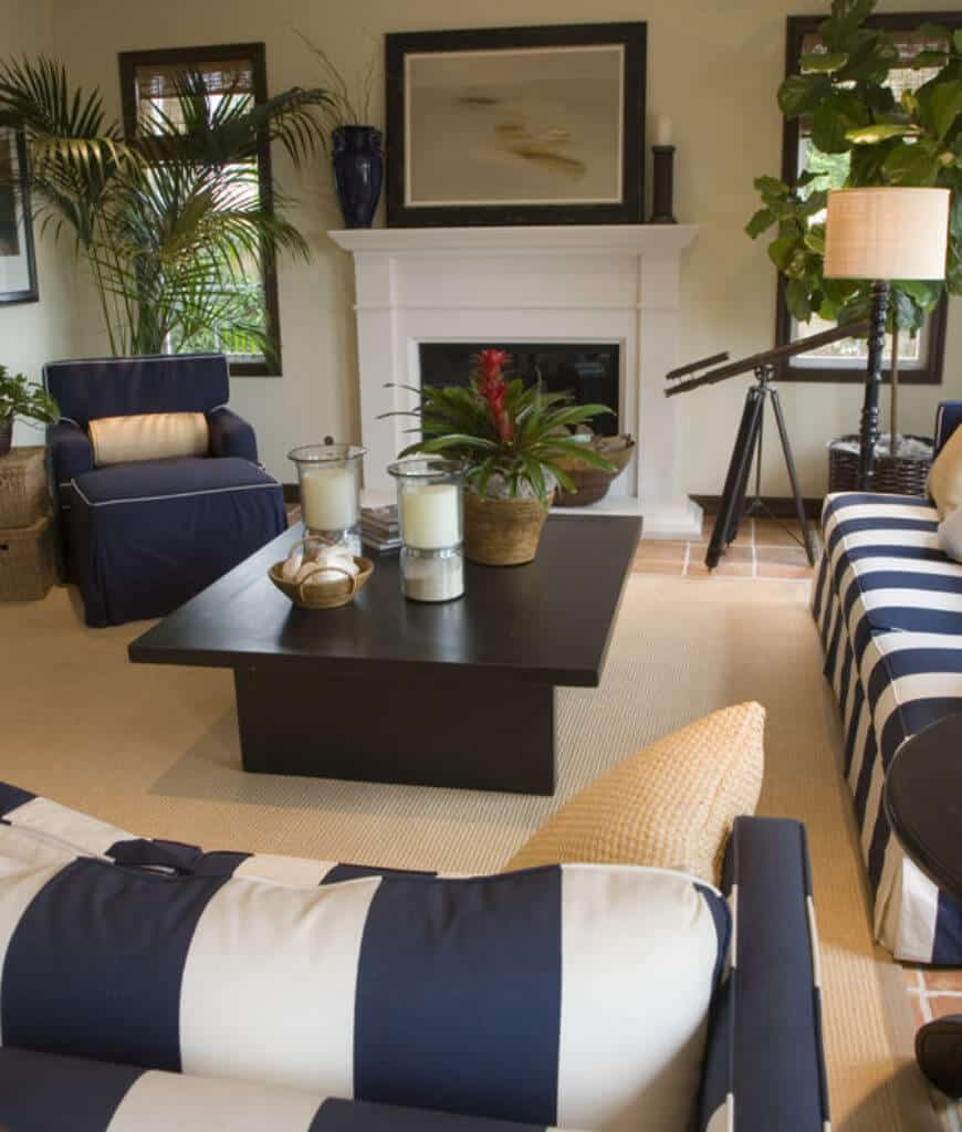 Tropical living room integrated with nautical theme showcasing striped sofas and navy blue armchair surrounding a wooden coffee table that sits on a jute rug.