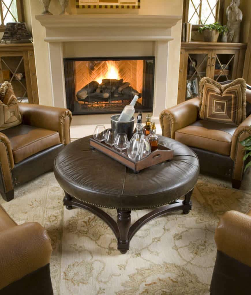 Sophisticated living room boasts a chevron fireplace and round ottoman surrounded with brown leather armchairs over a classic rug.