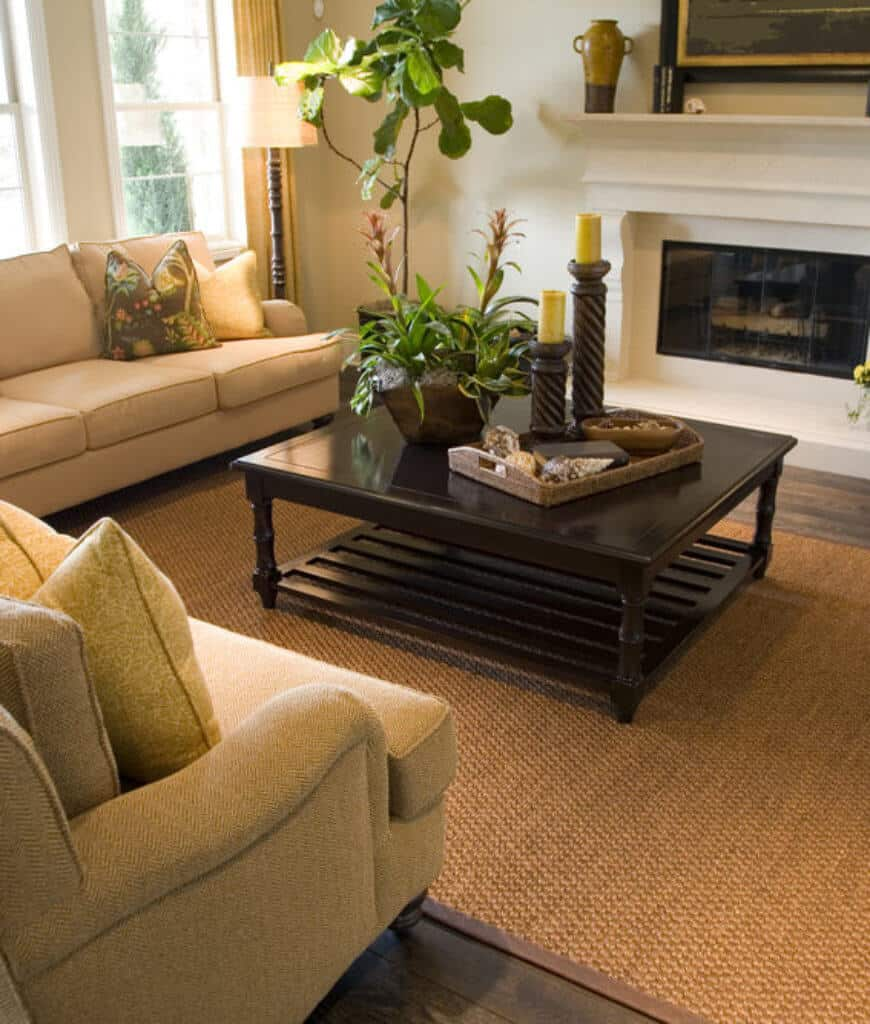 Warm living room features a white fireplace and wooden coffee table paired with beige sectional sofas that sit on a woven rug over wood plank flooring.