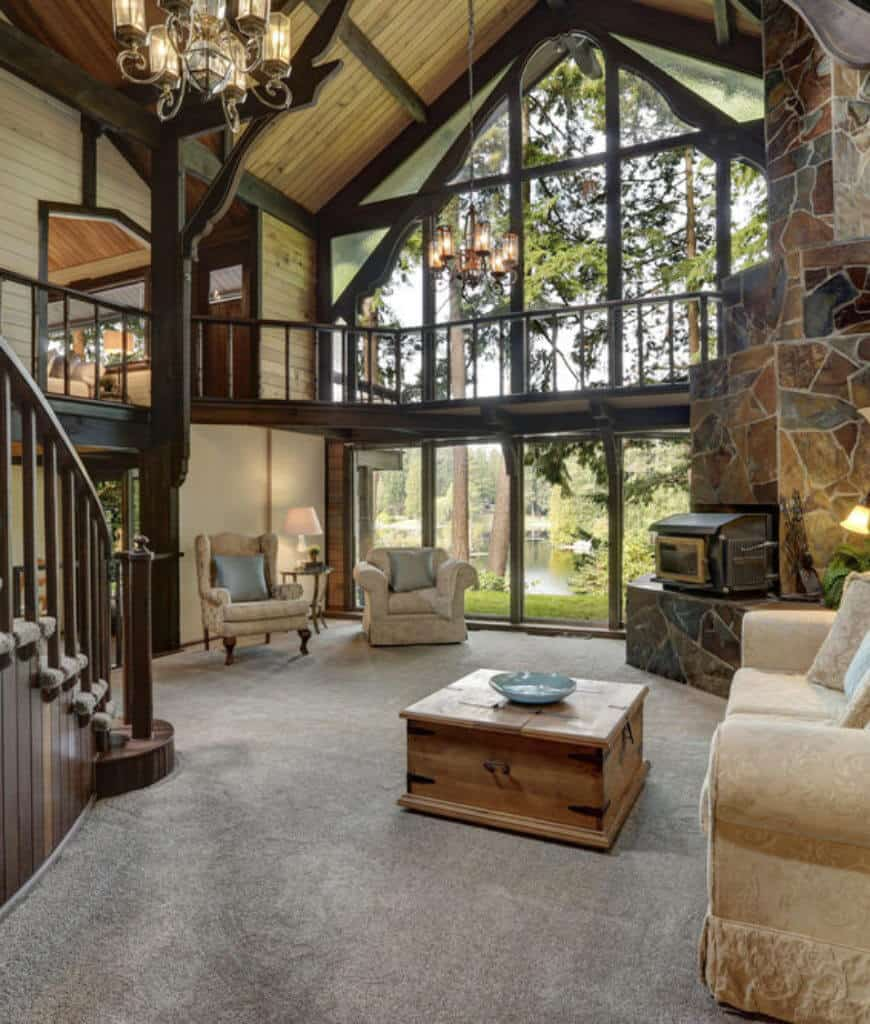Rustic living room boasts carpet flooring and high wood beam ceiling with hanging chandeliers. It includes classy beige seats and a fireplace fixed to the flagstone wall.