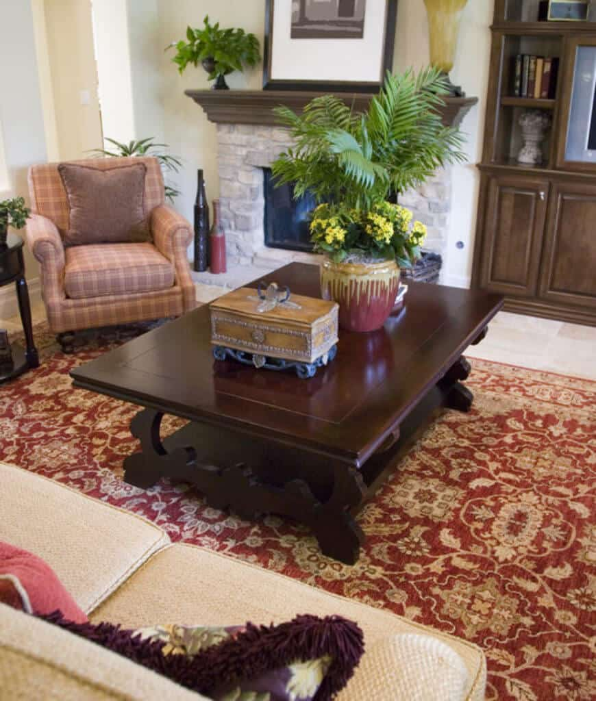 The classic living room showcases a red patterned rug that lays on marble flooring and a stone fireplace lined with a wooden mantel.