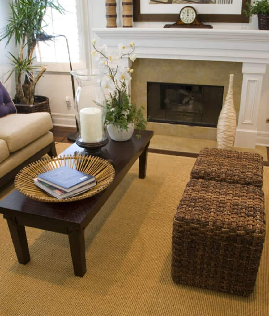 A rectangular coffee table sits on a jute rug in this living room with wicker stools and fireplace topped with a wooden mantel clock.