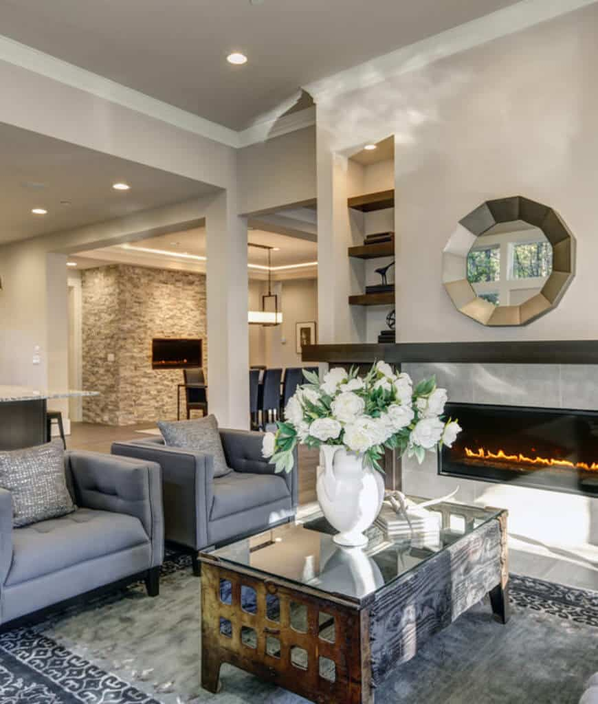 Stylish living room decorated with a round mirror that hung above the fireplace lined with a dark wood mantel. It has gray tufted armchairs and a rustic coffee table topped with a lovely flower vase.