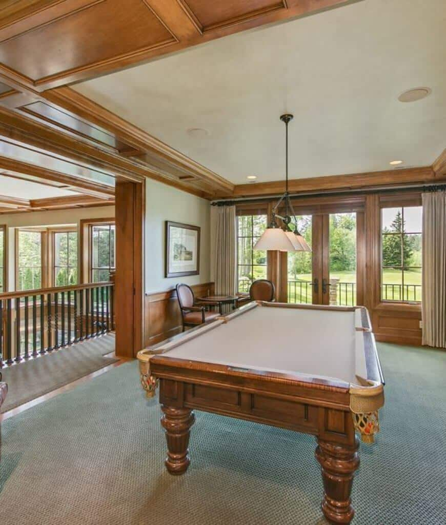 An airy room with framed windows and a French door overlooking the serene outdoor greenery. It has beige walls and ceiling lined with wooden panels that complement with the pool table.
