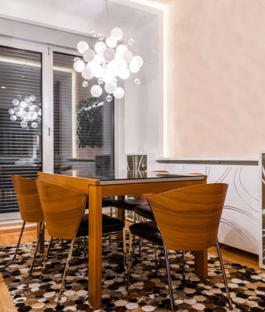 Contemporary dining room accented with a stylish chandelier and an eye-catching rug that lays on the hardwood flooring.