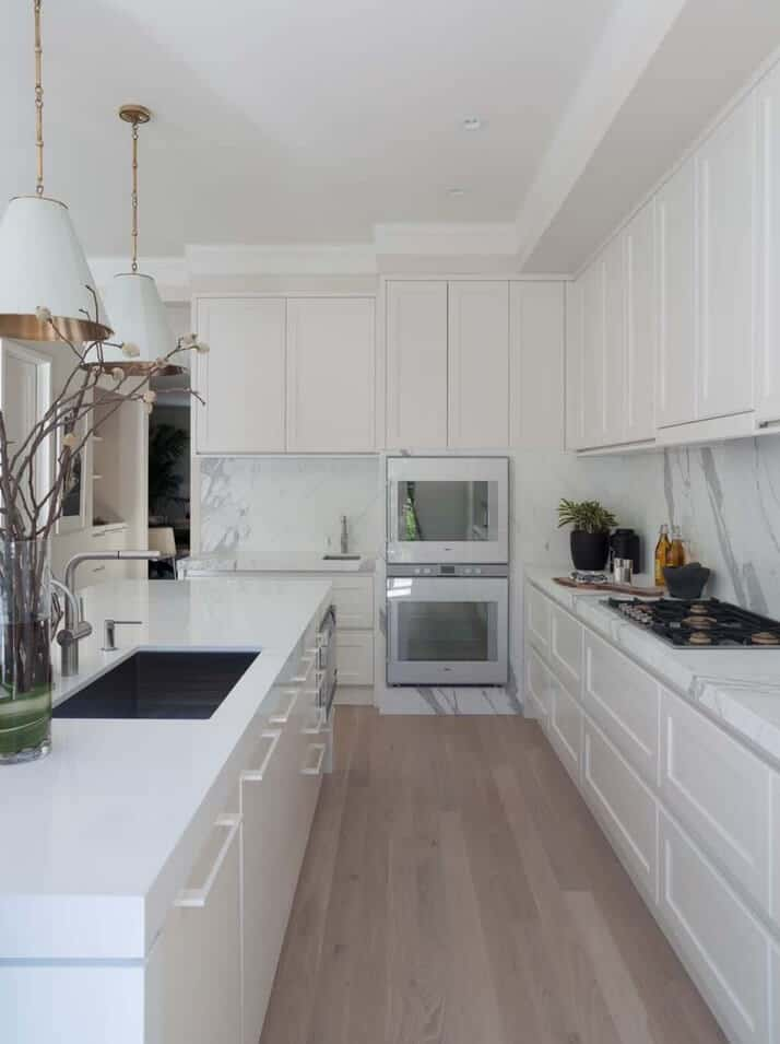 This kitchen boasts white cabinetry and double wall oven fixed against the marble backsplash. It has a kitchen island fitted with a sink and lighted by classy pendants.