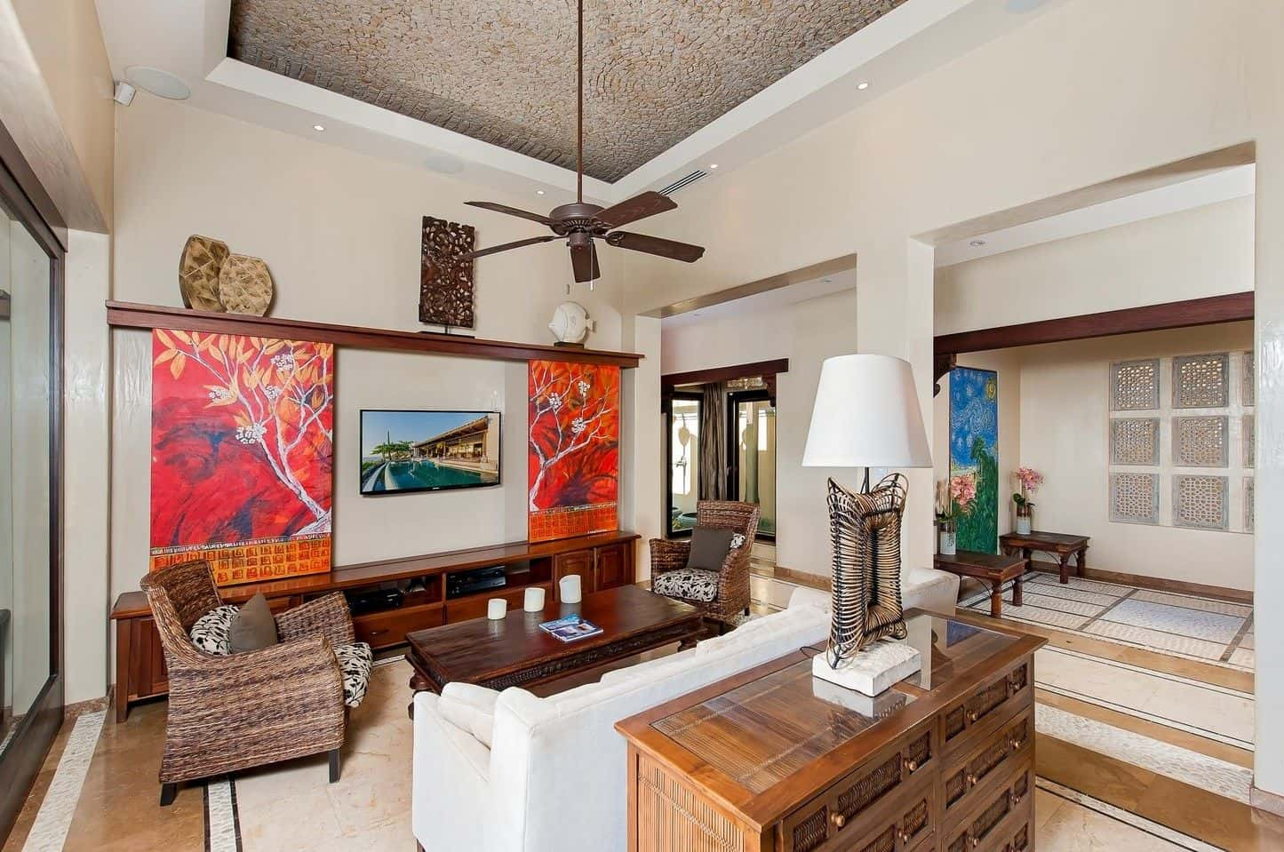 Charming living room decorated with a pair of lovely wall arts mounted above the TV stand. It has marble flooring and a stylish tray ceiling with a hanging vintage fan.