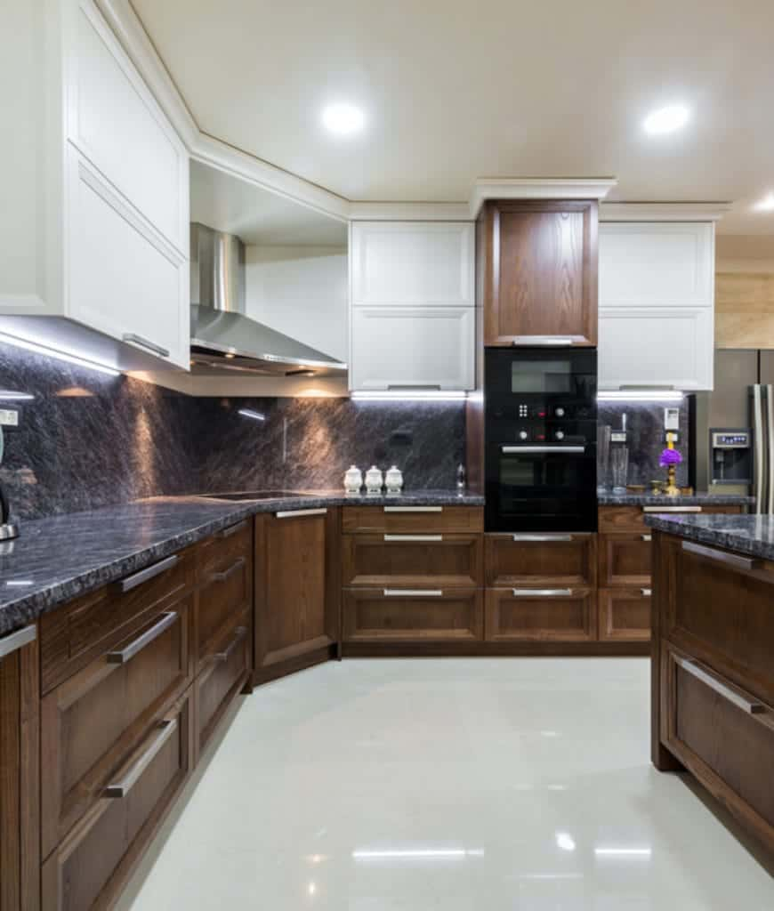 Black appliances add a modern look in this classic kitchen with white and wooden cabinetry. It is illuminated by recessed ceiling lights along with strip lights mounted on the gray marble backsplash.