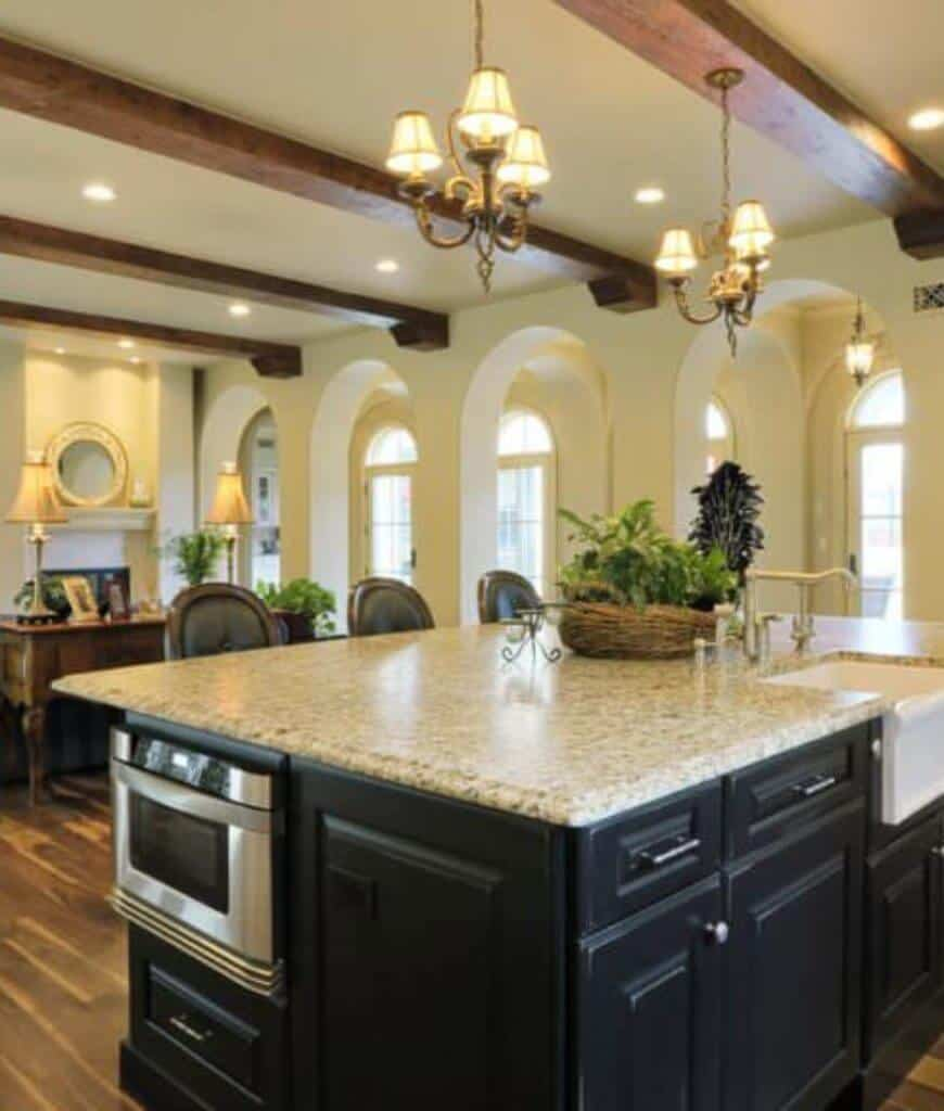 Cozy kitchen framed with open archways and wood beams boasts shade chandeliers and a black kitchen island fitted with a stainless steel oven and white vessel sink.