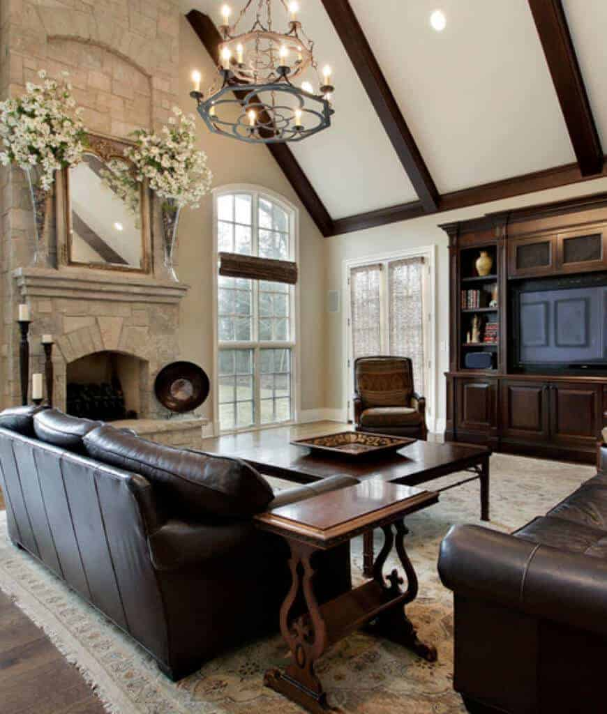A framed mirror hangs above the stone brick fireplace in this living room illuminated by a candle chandelier that hung from the cathedral ceiling lined with wood beams.