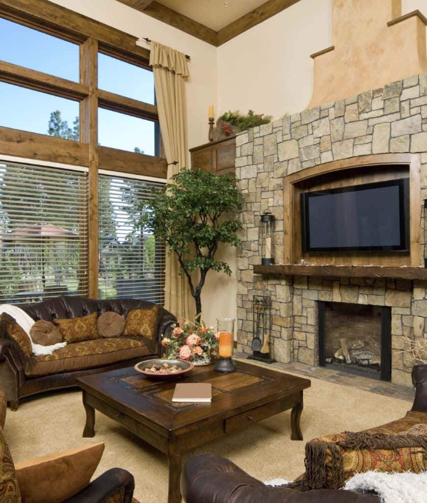 This living room features a television mounted on the wooden inset fixed to the stone accent wall with a fireplace at the bottom. It is accented with an indoor plant that gives a refreshing ambiance to the area.