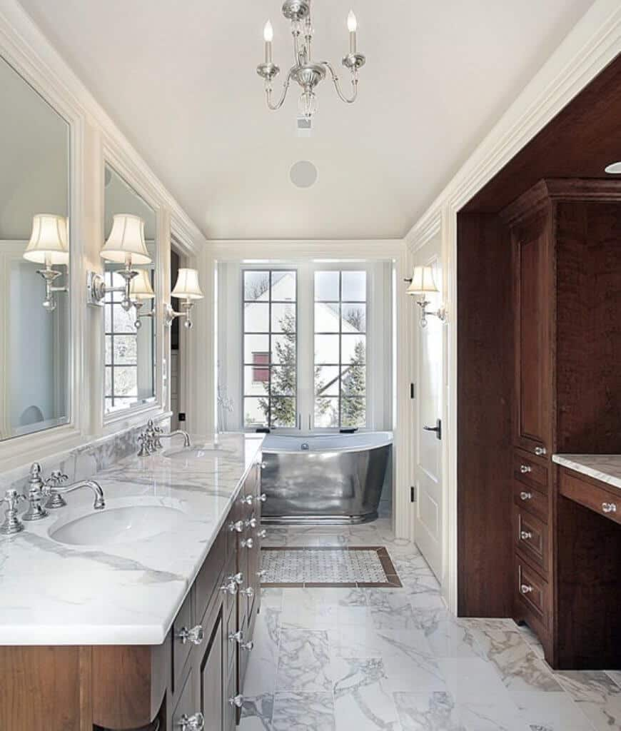 White primary bathroom offers a wooden dual sink vanity with chrome faucet complementing with the wall sconces and candle chandelier along with the freestanding tub by the french door.
