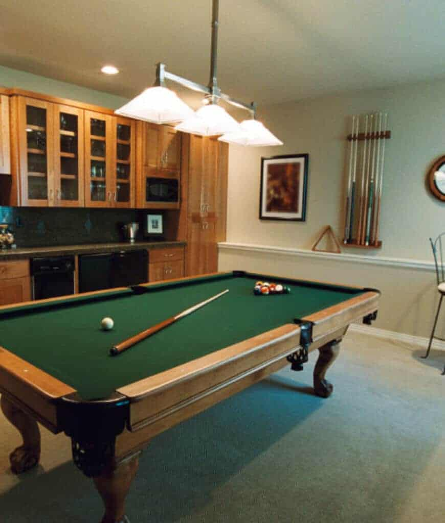 A traditional pool table with a cue stick wall rack on the side situated beneath the pendant light. The room has carpet flooring and built-in cabinetry fitted with marble countertop.