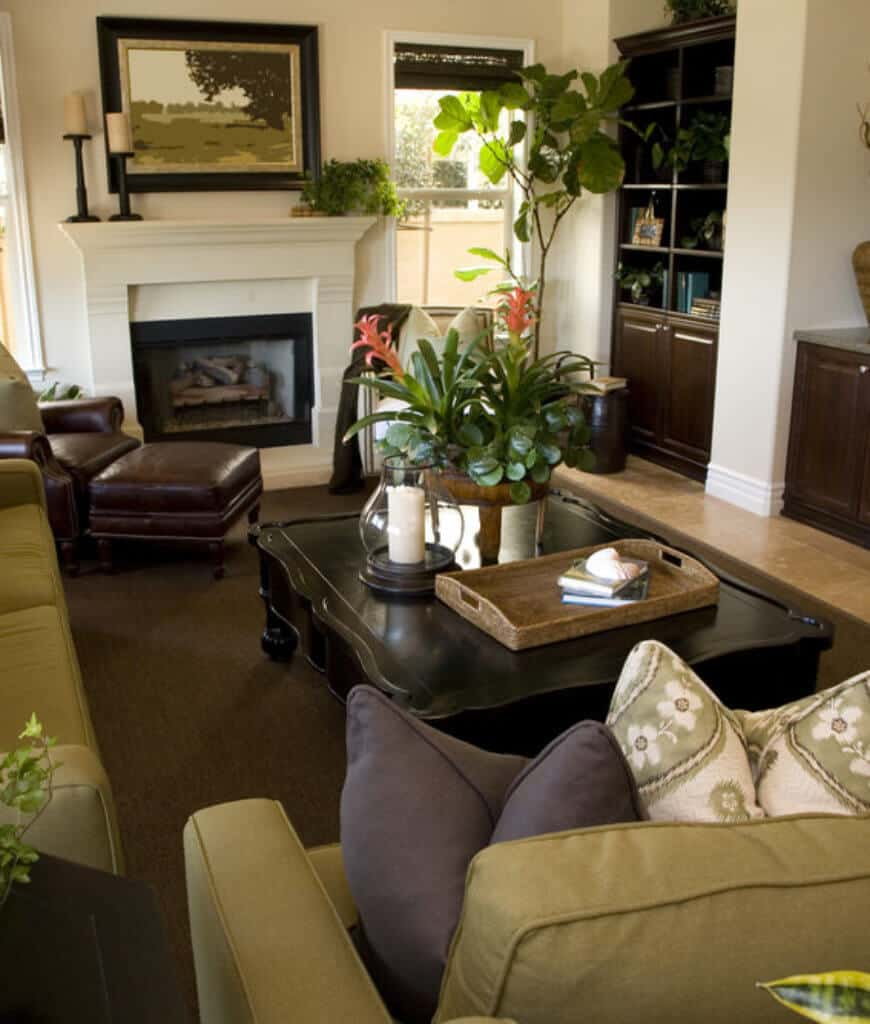 Fresh living room furnished with a leather lounge chair and a black coffee table along with green sectionals filled with fluffy pillows.
