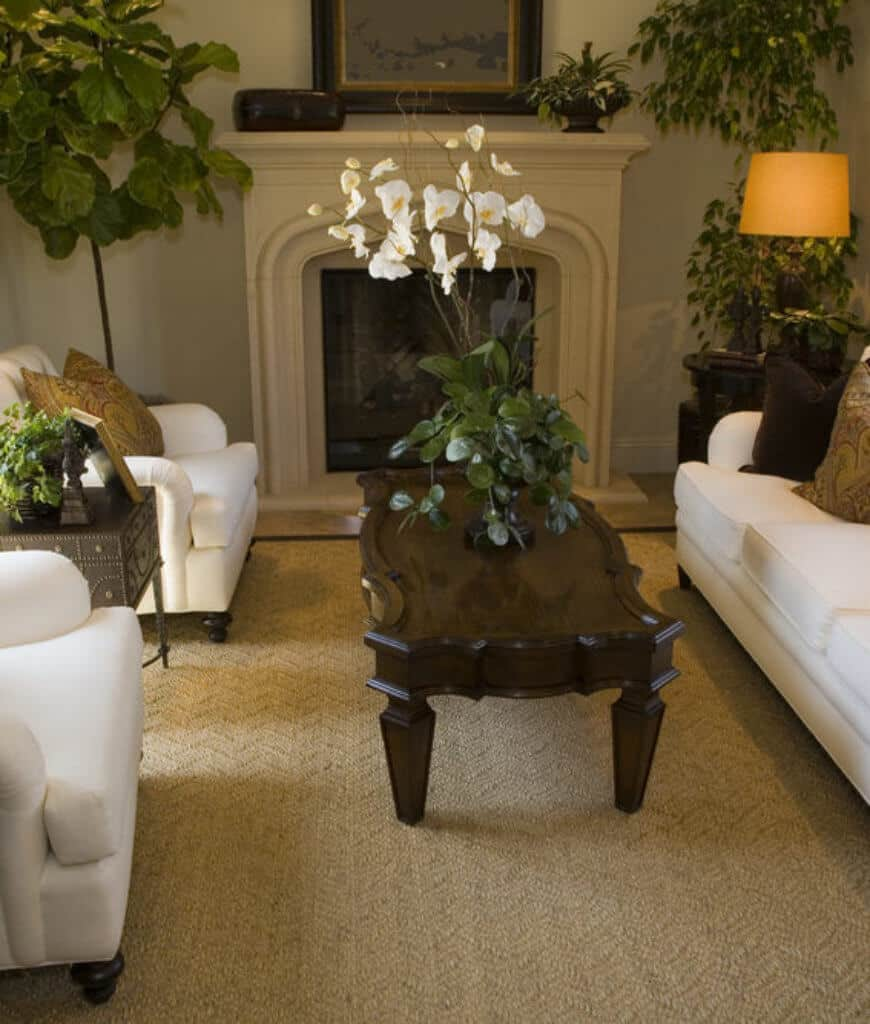 Neutral living room with white armchairs and sectional along with a dark wood coffee table and fireplace accented with indoor plants that add life to this room.