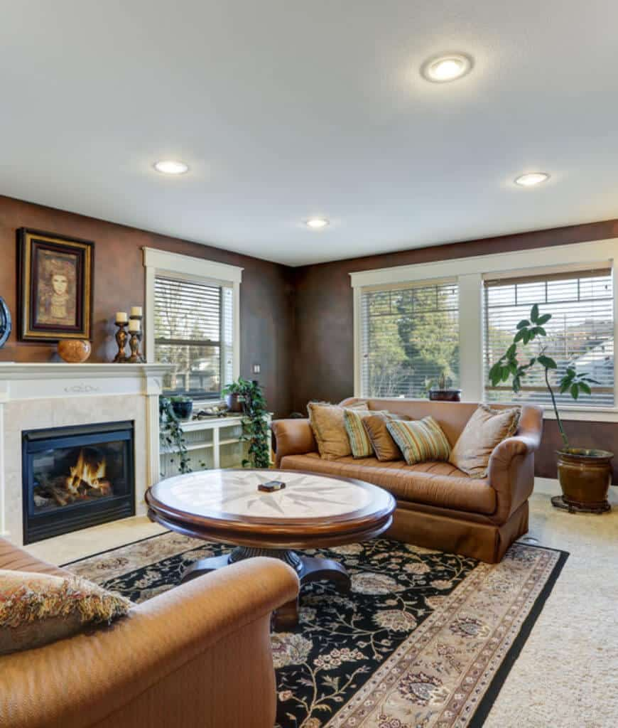 Tropical living room with brown facing sofas and a round coffee table that sits on a black floral rug over carpet flooring. It includes a fireplace with marble surround tiles and white ornate mantel.