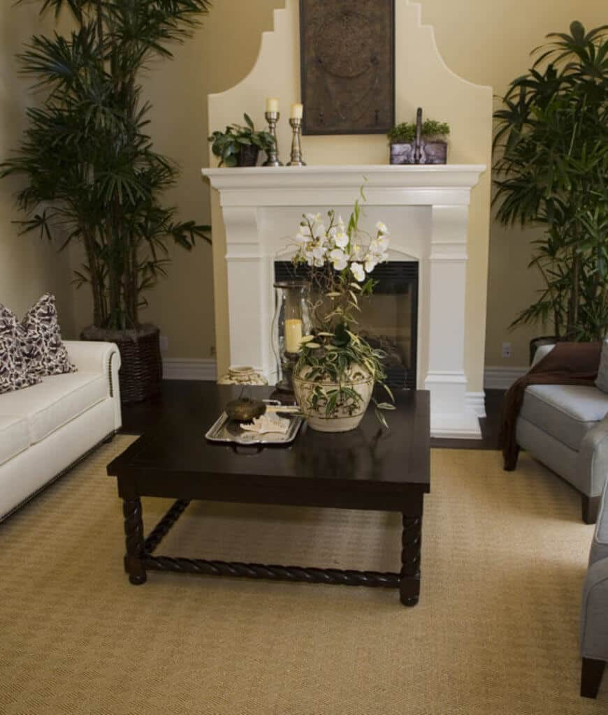 A gorgeous vase and candle sit on a wooden coffee table in this living room featuring comfy seats and white fireplace enclosed in glass.