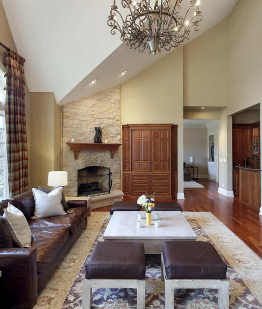 Cozy living room offers a built-in cabinet next to the corner fireplace covered with wrought iron fence along with a brown leather sofa and stools with a square coffee table in the middle.