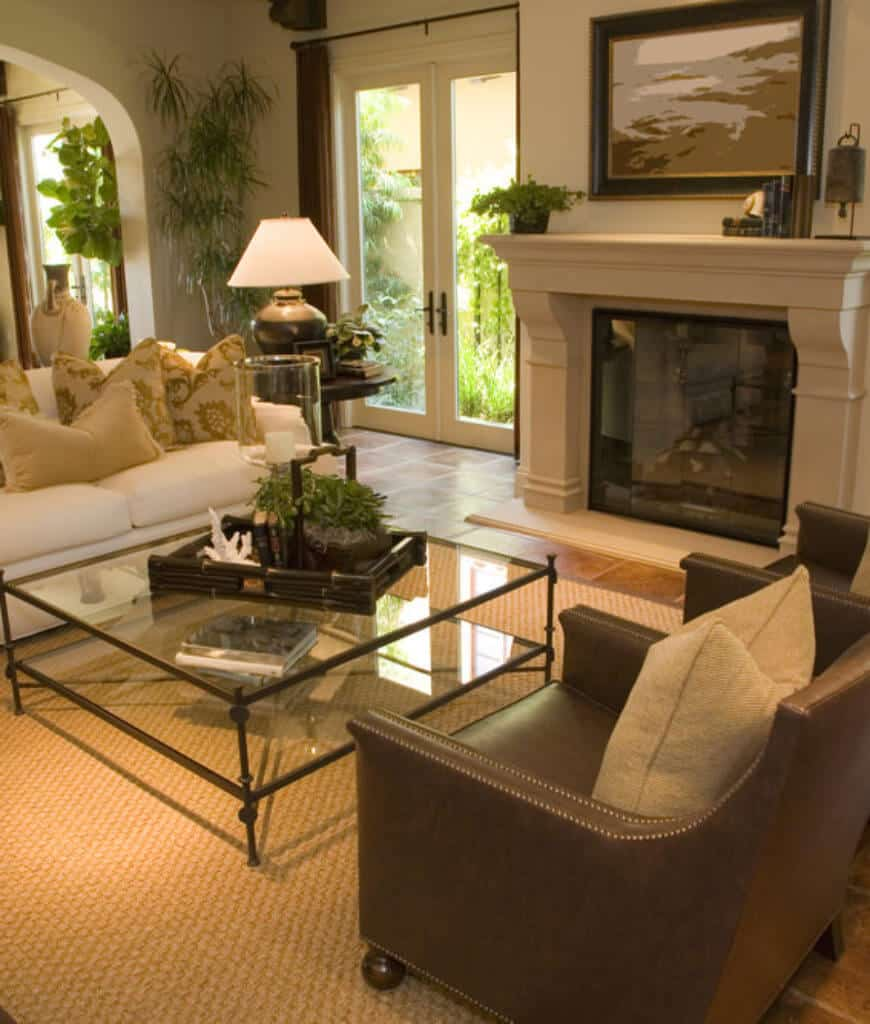 Tropical living room showcases a glass coffee table in between white sectional and leather armchairs that sit on a jute rug. The low ambient light from the floor lamp creates a romantic and warm vibe in this room.