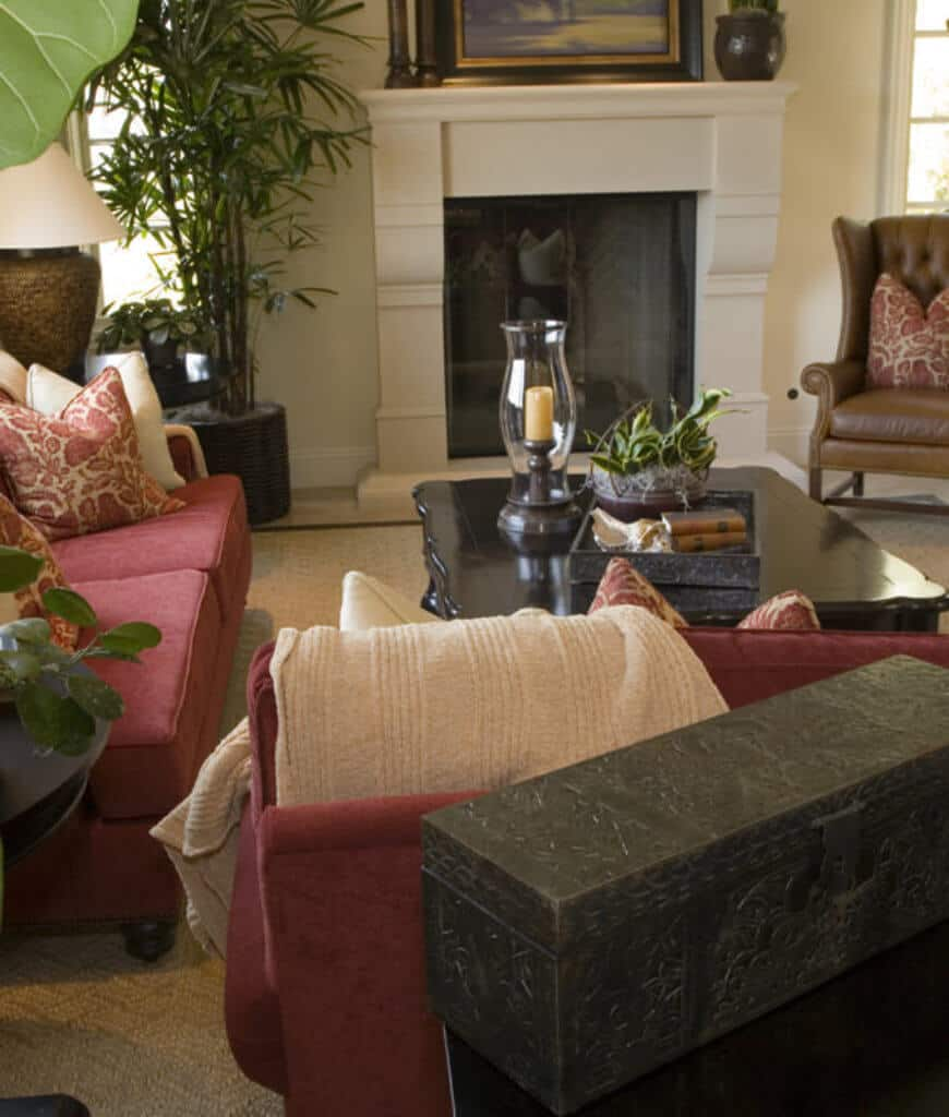 This living room with a black coffee table and white fireplace is accented with potted plants and red sofas filled with floral pillows.