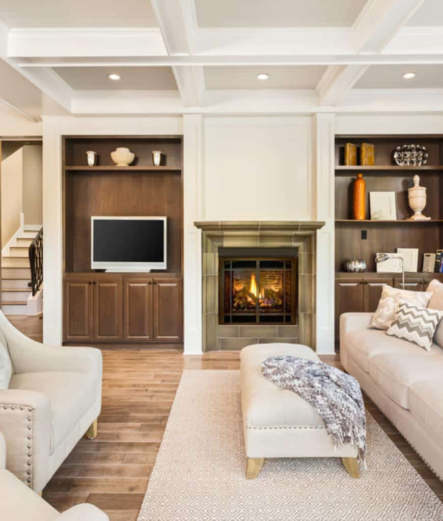 White living room with coffered ceiling and natural wood plank flooring topped by a patterned rug. It includes classy beige seats and a green brick fireplace in between built-in cabinets.